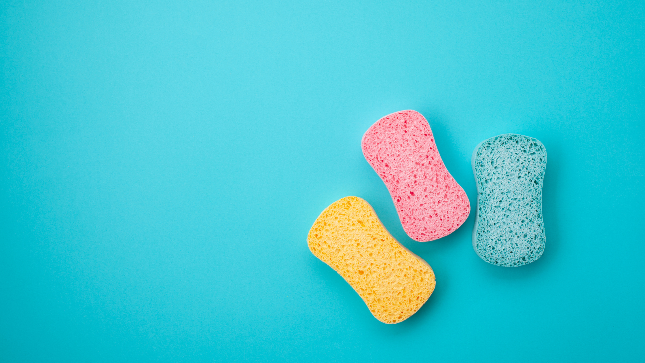 teal background with three sponges that are yellow, pink, and blue