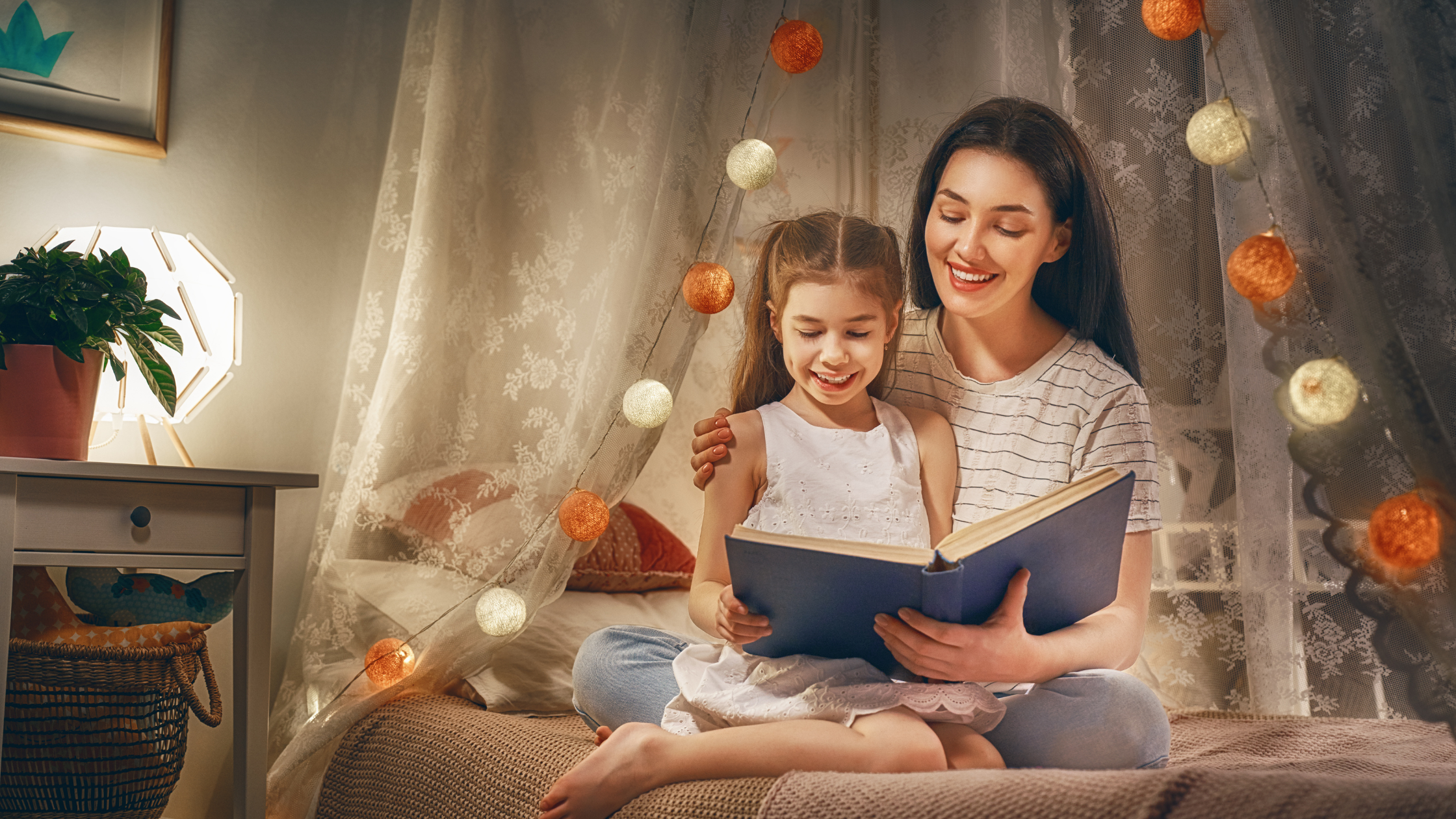 mother and daughter reading book on a bed
